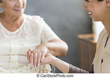 Nurse holding hands with senior