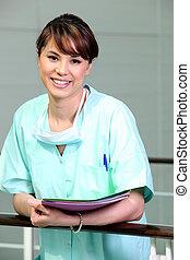Nurse in scrubs holding files