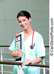 Nurse in scrubs with a clipboard