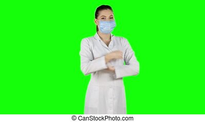 Nurse in surgery puts off the mask and smile. Green screen