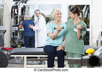 Nurse Instructing Senior Patient Exercising With Dumbbell