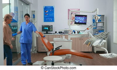 Nurse inviting next patient in stomatology room showing to lie on chair. Dentistry assistant sitting in consultation dental room with elderly woman while doctor speaking with old man in background.