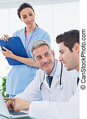 Nurse listening to doctors talking about something on their laptop in medical office