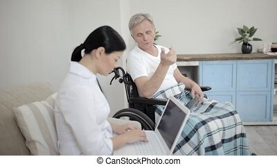 Nurse looking after disabled man - Nurse Typing Message On...