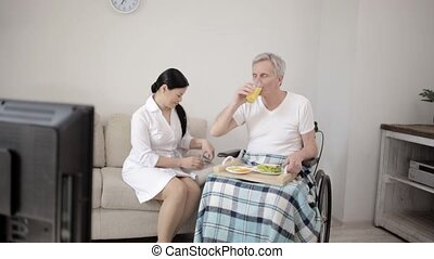 Nurse looking after disabled man - Old Disabled Man In...