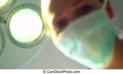 Nurse looking at a patient waking u - Video of a nurse...