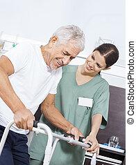 Nurse Looking At Senior Patient Using Walker In Rehab Center
