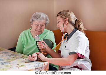 nurse measures blood pressure of an elderly woman