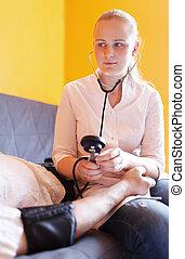 Nurse measures the patient blood pressure