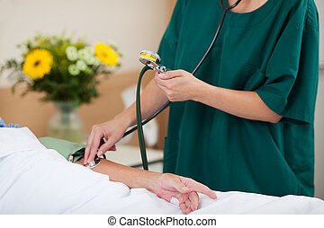 Midsection of nurse measuring blood pressure while looking at meter in hospital