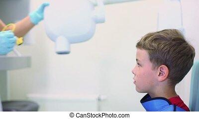 Nurse moves apparatus for x-ray photography closer to boy