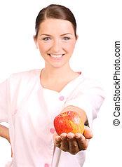 Nurse offering an apple - A beautiful young nurse offering...