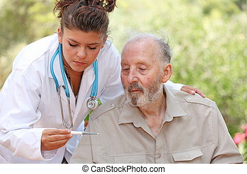 nurse or doctor taking temperature of senior patient