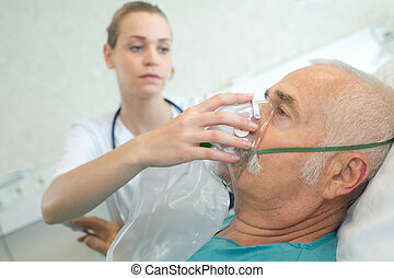 Nurse placing oxygen mask on patient