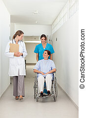 Nurse pushing a patient in a wheelchair while talking to a doctor in a hospital hallway