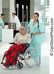 Nurse pushing an older woman in a wheelchair