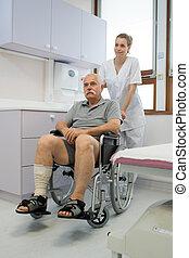 nurse pushing disabled senior man in the hospital