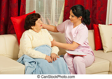 Nurse put a pillow to senior woman - Nurse caring a senior...
