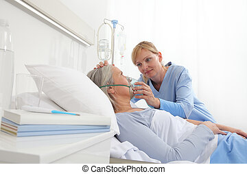 nurse puts oxygen mask on elderly woman patient lying in the hospital room bed
