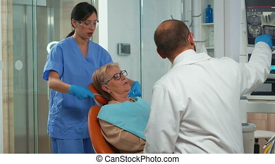 Nurse putting dental bib to old woman during stomatological examination. Doctor and nurse working together in modern orthodontic clinic showing radiography of teeth on monitor pointing on digital screen