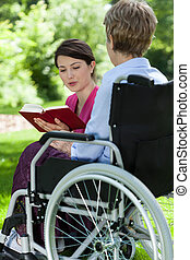 Nurse reading a book with older woman