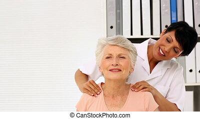 Nurse rubbing elderly patients shoulders