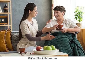 Nurse serving coffee to senior - Young nurse serving coffee...