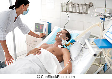 Intensive care unit. Young lady in white lab coat checking digital device for measuring blood pressure. Middle aged man with endotracheal tube in mouth sleeping after surgery