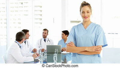 Nurse smiling at camera while staff are working behind her...
