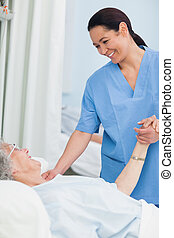 Nurse smiling to a patient while holding her hand in...