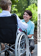 Nurse smiling to elderly woman on wheelchair