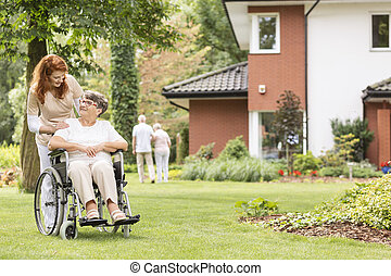 Nurse supporting disabled senior woman in the wheelchair in the garden