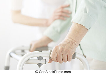 Nurse supporting eldery person - Nurse in white uniform...