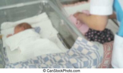 Nurse swaddles newborn infant in medical chamber - Nurse...