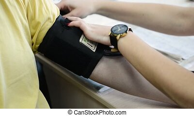 Nurse taking blood pressure for man. Close up of doctor care patient.