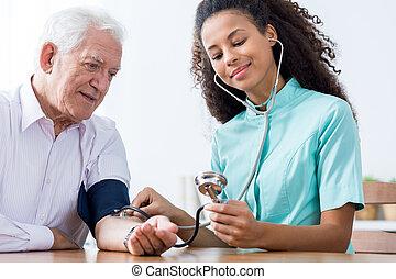 Nurse taking blood pressure - Photo of old male and nurse...