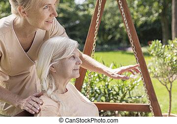 Nurse taking care of a senior in a garden