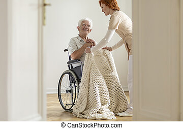 Nurse taking care of happy elderly man in the wheelchair in a house