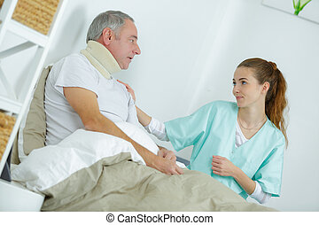 nurse taking care of injured man in bed at home