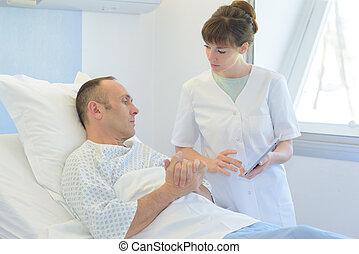 nurse taking care of patientin hospital room
