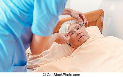 Nurse taking care of sleeping senior woman in the nursing home
