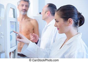 nurse taking scan of male patients abdomen