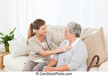 Nurse taking the heartbeat of her patient at home