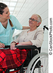 Nurse talking to an elderly lady in a wheelchair