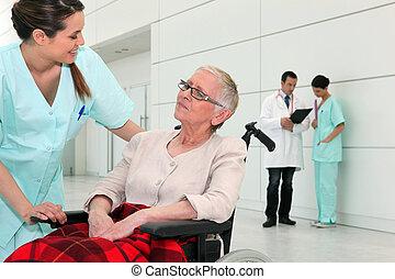 Nurse talking to an elderly woman in a wheelchair
