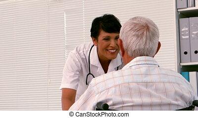Nurse talking to an old man in a w