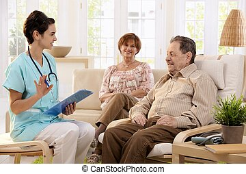 Nurse talking to elderly patients at home