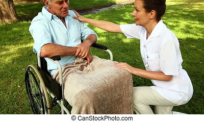 Nurse talking to man in wheelchair outside on a sunny day