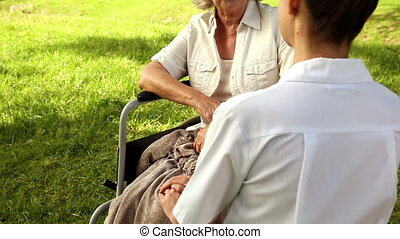 Nurse talking to woman in wheelchair outside on a sunny day