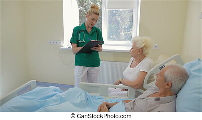 Nurse talks with male patient and his wife
